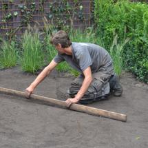 Foto van medewerker Groen bezig grond te effenen, tevens link naar pagina Groenvoorziening.