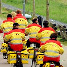 Foto van groep postbezorgers op de fiets in de vrolijke kleuren geel en oranje.