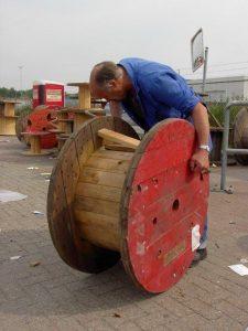 Foto van medewerker die een houten haspel repareert.
