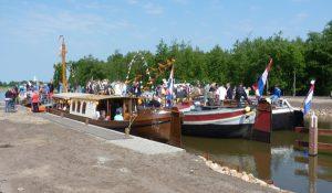 Foto van aangemeerde boten met veel vertoon van vlaggen.