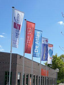 Foto van wapperende vlaggen voor de hoofdingang.